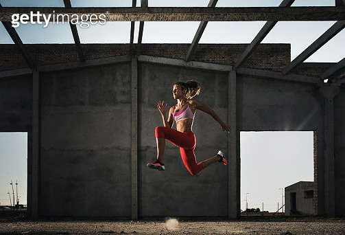 Dedicated woman jumping in a run on a sports training. - gettyimageskorea