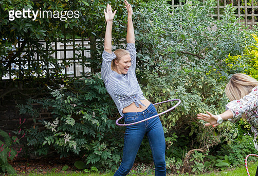 Laughing playful woman spinning in plastic hoop in garden - gettyimageskorea