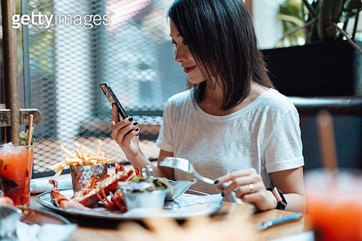 Young Woman Using Smart Phone While Eating At Seafood Restaurant - gettyimageskorea