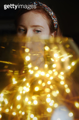 Redhead teenager girl standing behind the large glass jar with Christmas string light. Nicely fits for book cover - gettyimageskorea