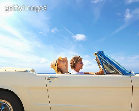 Caucasian couple driving convertible under blue sky - gettyimageskorea