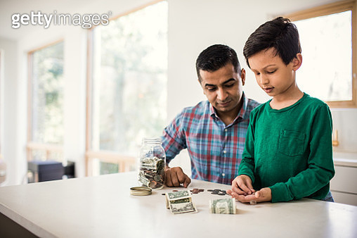 Father and son counting money at home - gettyimageskorea