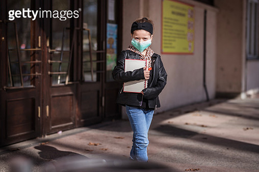 Scared young child with protective mask and books in her hands exiting school - gettyimageskorea