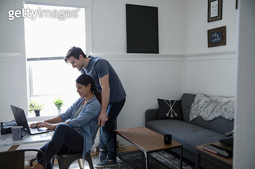Young couple using laptop in living room - gettyimageskorea