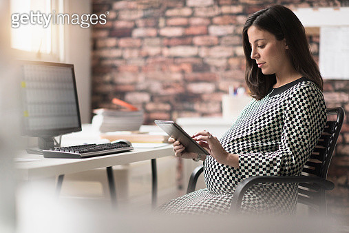 USA, New Jersey, Pregnant woman working in office - gettyimageskorea