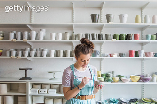 Young female potter using hand tool on vase while standing against shelves at store - gettyimageskorea