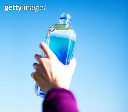 Woman Holding Bottle Against Blue Sky - gettyimageskorea