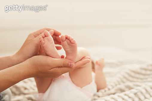 Mother holding feet of baby - gettyimageskorea