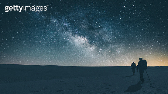 Two people hiking-backpacking at night across White Sands National Park illuminated by a glare from Milky Way Galaxy. - gettyimageskorea