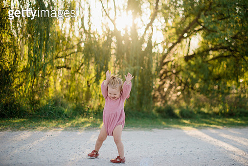 baby girl playing on dirt road at sunset - gettyimageskorea