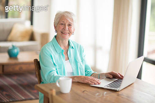 Senior woman using computer at home - gettyimageskorea