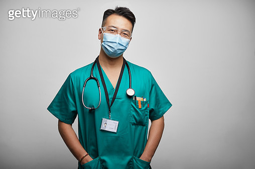 Asian Doctor/Nurse With Hands in Pockets On White Background - gettyimageskorea