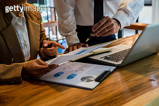 Midsection Of Businessmen Working Over Graph On Table In Office - gettyimageskorea