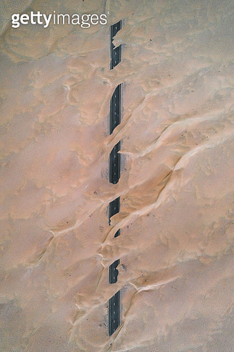 Dunes crossing a straight road in the desert, Dubai, United Arab Emirates - gettyimageskorea