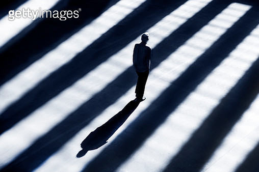 Person's shadow in striped lighting. Man standing perfectly still. - gettyimageskorea