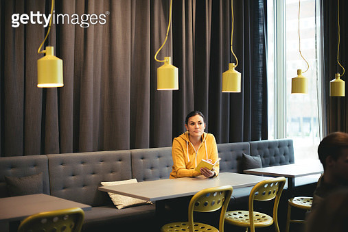 Mid adult businesswoman with book sitting at table in cafeteria at office - gettyimageskorea