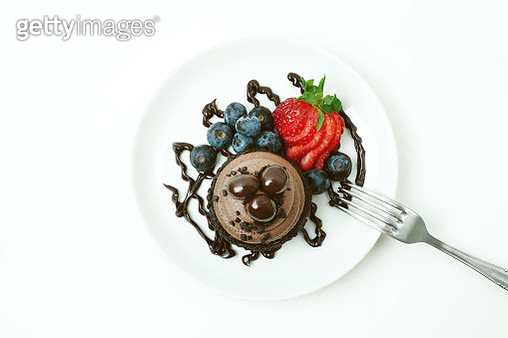 Home-baked chocolate cupcakes with fresh berries and chocolate covered espresso beans on a white background with plate and fork. - gettyimageskorea