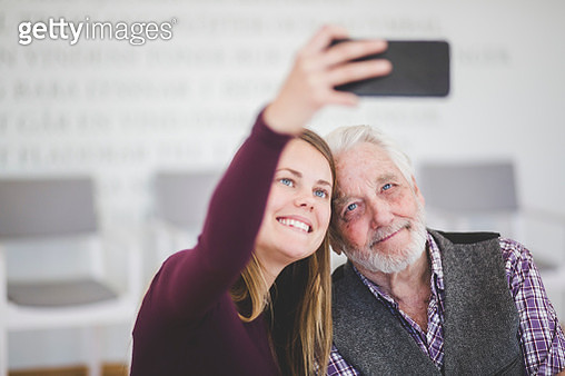 Smiling young woman taking selfie with grandfather while sitting in nursing home - gettyimageskorea