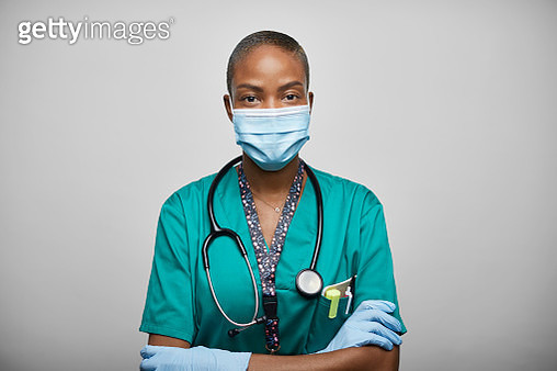 African American Doctor/Nurse With Arms Crossed Against White Background - gettyimageskorea