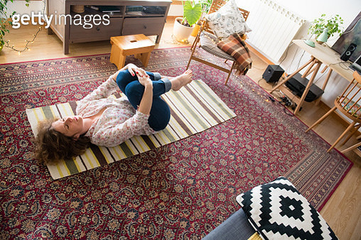 Woman lying on the floor and doing yoga at home - gettyimageskorea