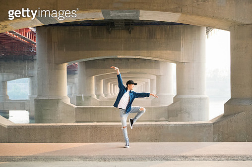 Young street dancer dancing solo under bridge with sunset. - gettyimageskorea