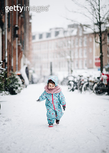 Cute Girl Walking On Snowy Field In City - gettyimageskorea