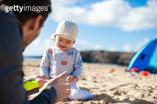 Spain, Lanzarote, happy baby girl playing with father on the beach - gettyimageskorea
