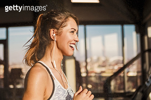 Happy sweaty woman running on treadmill in a gym smiling - gettyimageskorea