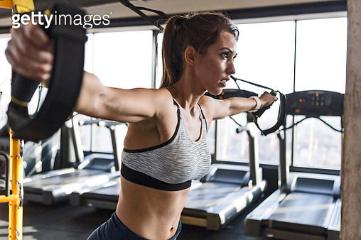 Young woman training with suspension straps at a gym - gettyimageskorea