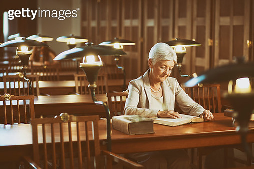 Senior woman reading an old book in the library - gettyimageskorea