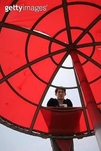 Low Angle Portrait Of Teenage Boy Standing By Parasol - gettyimageskorea