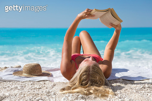 woman, reading book, lying on towel on sunny beach - gettyimageskorea