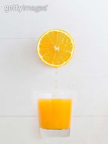 Orange Dripping Juice Over A Orange Juice Glass - gettyimageskorea