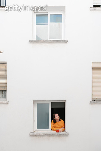 Caucasian woman in yellow sweater is at the window having a cup of coffee - gettyimageskorea