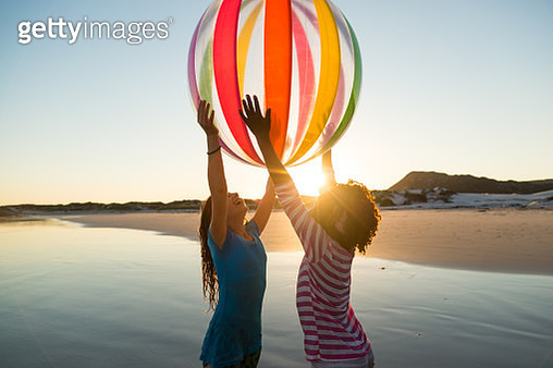 Children playing on a beach at sunset - gettyimageskorea