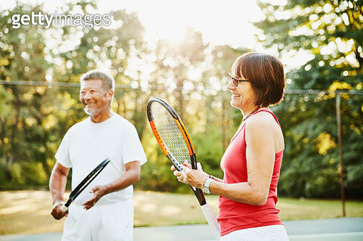 Laughing senior friends in discussion at net during early morning tennis match - gettyimageskorea
