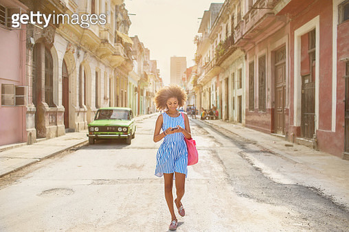 Cuban girl looking at mobile phone, walking down street in Havana - gettyimageskorea