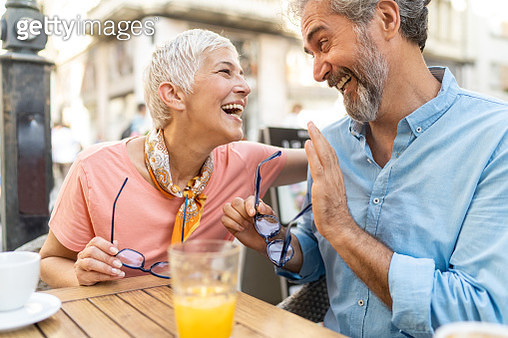 Mature couple have fun in outdoor cafe - gettyimageskorea