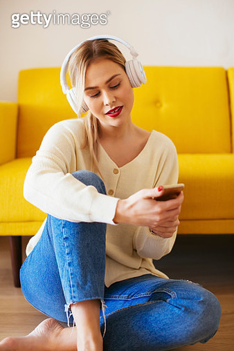 Blonde woman with headphones using smartphone at home - gettyimageskorea