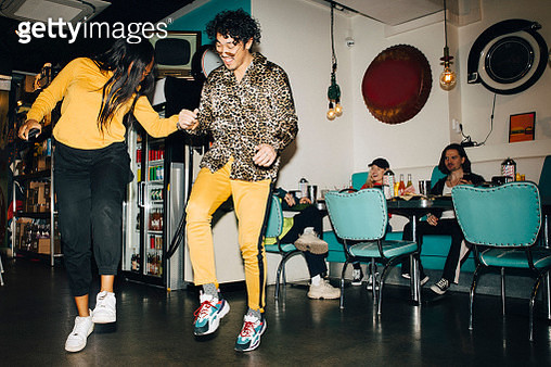 Smiling young man and woman dancing while friends watching in background in cafe - gettyimageskorea