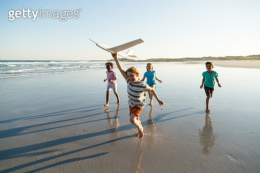 Group of children running along a deserted beach with a model plane - gettyimageskorea