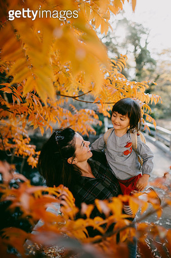 Mother and child under red autumn leaves, Tokyo, Japan - gettyimageskorea