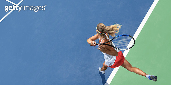 A top view of a professional female tennis player having just served the ball during a tennis match. The athlete wears a white tennis top with red skirt, and is playing on a tennis court with a blue and green hard surface in hot and sunny conditions durin - gettyimageskorea