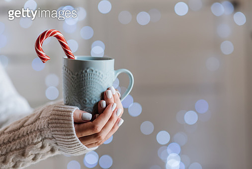 Famale hands holding a cozy ceramic handmade mug with coffe. Winter and Christmas home time concept. Lifestyle. Copy space. - gettyimageskorea