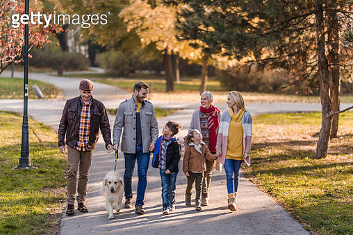 Happy extended family taking a walk with their dog in autumn day. - gettyimageskorea