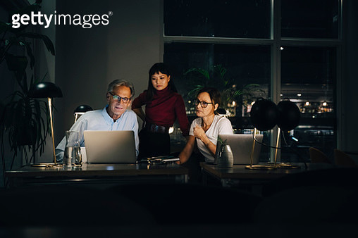 Senior businessman planning strategy with female colleagues at coworking space in dark - gettyimageskorea