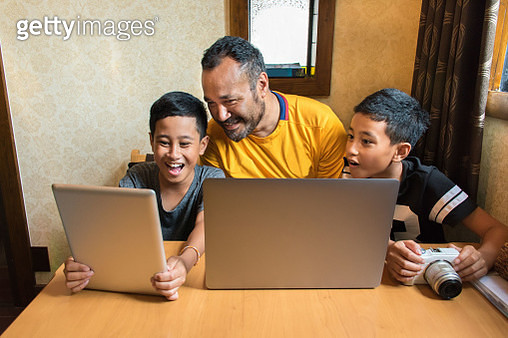 Candid Front Portrait of Twin Boys with Polynesian Father Using a Computer, Tablet, and Camera - gettyimageskorea