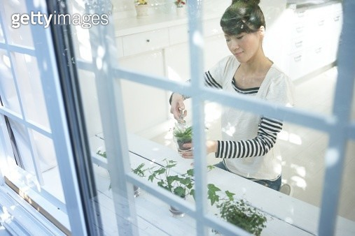 Young woman watering potted plants - gettyimageskorea