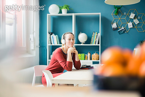 Woman with eyes closed sitting at table lisening music with headphones - gettyimageskorea