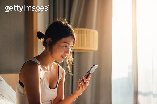 Young Woman Using Smartphone While Waking Up In Bed - gettyimageskorea